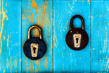 Two Ancient And Rusty Closed  Padlocks On Old Wooden Table Covered With Blue Paint. View From Above