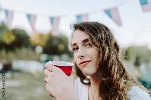 Obraz na plátně Chica joven con vaso rojo sentada junto a una caravana con la bandera de estados