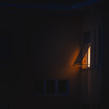 Light Coming Out Of The Window Of An Apartment Building At Night