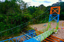 Aerial Side View Of A Metal, Pedestrian Bridge In The Colors Green, Blue And Orange That Is Leading Away From A Playground