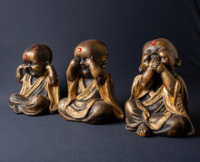 Three Small Buddhas With Different Expressions On A Dark Black Background. One Buddha With A Blind Expression, Another With An Outbreak Expression And The Third Mute.