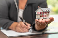 Woman Signing Real Estate Contract Papers Holding Small Model Home In Front.