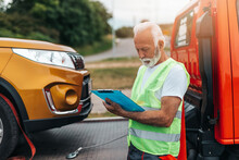 Handsome Senior Man Working In Towing Service On The Road. Roadside Assistance Concept..