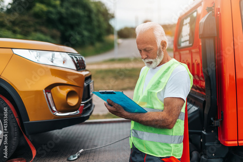 Fotografie, Obraz Handsome senior man working in towing service on the road