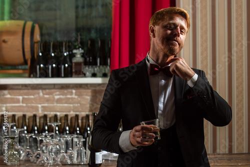 Obraz Stylish man drinking whiskey. Alcohol at bar. Man at pub. - fototapety do salonu