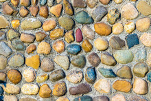 Multi-colored And Multi-textured Pebble Stones Lie In Rows Partially Pressed Into The Main Covering Of A Horizontal Or Vertical Surface
