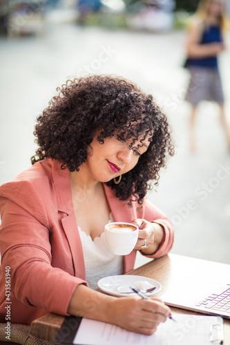 Obraz Business woman sitting in café writing on document. - fototapety do salonu