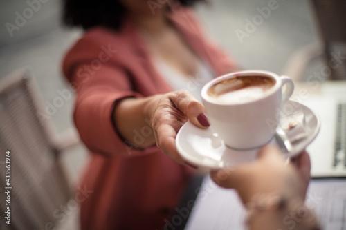 Obraz Woman at café taking mug of coffee. Focus is on hand. - fototapety do salonu