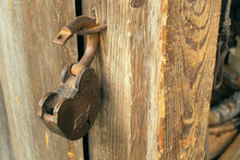Old Barn Door Lock Hanging On A Loop Against The Background Of Old Textured Wooden Walls Of Boards