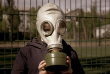 A Child In A Gas Mask. Boy In Personal Protective Equipment.