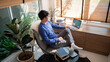 Young asian male tech user relaxing  holding laptop computer and looking at the screen in living room, Remote Job or work from home concept.
