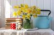 Leinwandbild Motiv bouquet of yellow daffodils in a glass jar, books and a mug.
