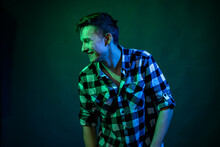 A Young Man Dances In The Studio With Blue And Green Light