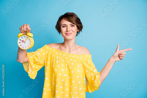 Photo portrait of girl with alarm clock pointing finger at blank space isolated Fotobehang