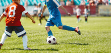 Children Playing Game On Football Soccer Stadium Field. Boys Compete During Soccer Tournament Match. Kids In Red And Blue Soccer Jersey Shirts