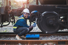 African Machine Engineer Technician Wearing A Helmet, Groves And Safety Vest Is Using A Wrench To Repair The Train