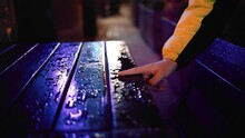 The Guy Runs His Finger Along The Wet Table On The Street, Moving The Water From The Table. Shooting Close-up In Slow Motion. Neon Light All Around