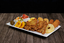 Cuban Fillet. Made With Breaded Steak, Banana, Breaded Cheese And Ham, French Fries With Bacon. Tomato Vinaigrette, Select Vegetables, Pineapple, Peach And Fig. Served In A Porcelain Dish.