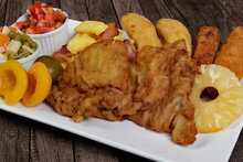 Tasty Cuban Filet. Made With Breaded Steak, Banana, Breaded Cheese And Ham, French Fries With Bacon. Vinaigrette, Vegetables, Pineapple, Peach And Fig. Served In A Porcelain Dish.