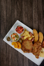 Cuban Filet. Made With Breaded Steak, Banana, Breaded Cheese And Ham, French Fries With Bacon. Vinaigrette, Vegetables, And Fruits. Served In A Porcelain Dish. Top View Photo With Top Space For Text.