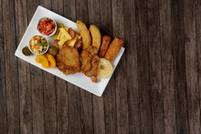 Cuban Filet. Made With Breaded Steak, Banana, Breaded Cheese And Ham, French Fries With Bacon. Vinaigrette, Vegetables, And Fruits. Served On The Porcelain Platter. Top View With Free Space For Text.