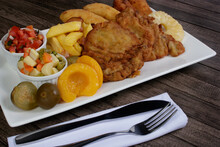 Cuban Filet. Made With Breaded Steak, Banana, Breaded Cheese And Ham. French Fries With Bacon. Vinaigrette, Vegetables, And Fruits. Served On The Porcelain Platter. Fork And Knife On Napkin.