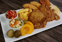 Cuban Filet. Made With Breaded Steak, Banana, Breaded Cheese And Ham. French Fries With Bacon. Vinaigrette, Vegetables, And Fruits. Served On The Porcelain Platter. Close-up. Brazilian Gastronomy.