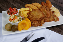 Cuban Filet. Made With Breaded Steak, Banana, Breaded Cheese And Ham. French Fries With Bacon. Vinaigrette, Vegetables, And Fruits. Served On The Porcelain Platter. White Napkin. Brazilian Gastronomy.
