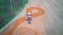 Red Tractor Makes A U-turn In The Field And Plows, Cultivates The Field On A Spring Day. Photo With A Drone