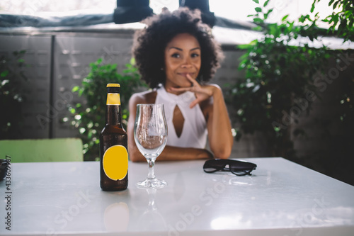 Obraz Smiling woman with bottle of beverage in summer cafe - fototapety do salonu
