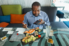 Food Photography And Blogging With Smartphone. Closeup Top Angle View Of Young Afro American Man Taking A Picture With His Smartphone Of A Plate With Japanese Food Sushi Rolls