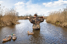 The Hunter Stands In The Water Next To The Plastic Duck Decoys
