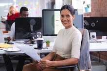 Portrait Of Indian Woman Holding A Document Smiling While Sitting On Her Desk At Modern Office