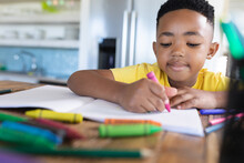 African American Boy Sitting At Table, Writing In Notebook