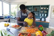 African American Father And Son In Kitchen, Cooking Together