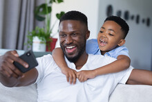 African American Father And Son Sitting On Sofa, Using Smartphone And Smiling