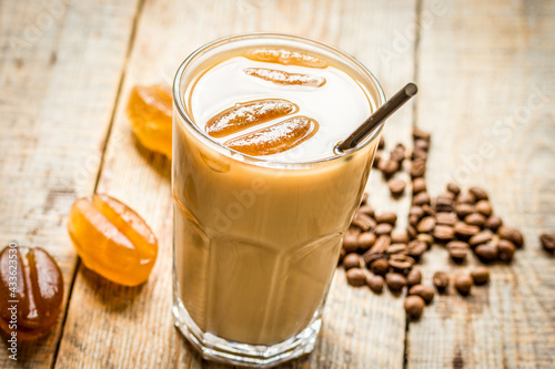 Obraz cold coffee glass with ice cubes on wooden table background - fototapety do salonu
