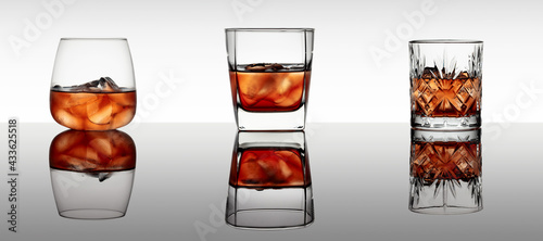 Obraz Three various glasses of whiskey with ice on a black reflective background. - fototapety do salonu