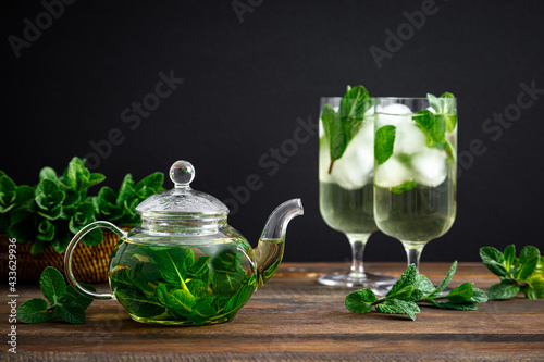 Iced mint tea, refreshing herbal drink in a glass with ice and fresh leaves on dark background - fototapety na wymiar