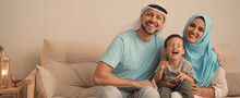 Happy Muslim Family On Sofa In Living Room, Space For Text. Banner Design