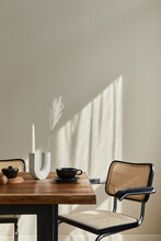 Minimalist Concept Of Dining Room Interior With Wooden Family Table, Design Chairs, Candle Stick, Cup Of Coffee, Tableware, Beige Wall And Personal Accessories. Copy Space. Template.