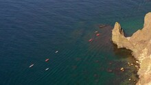 A Group Of Kayaks Sails Off The Beautiful Rocky Sea Coast Top View