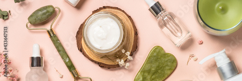 Cosmetic products - Jade roller and gua sha massager with cream and serum bottles at pastel background. Spa background. Top view with copy space.