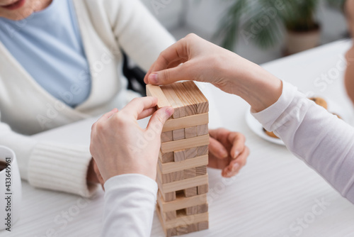 Murais de parede partial view of nurse playing wood blocks game with aged woman on blurred backgr