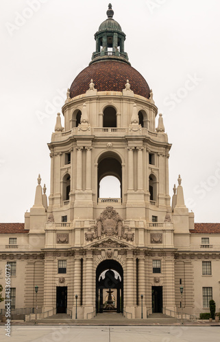 Fényképezés Pasadena, CA, USA - May 11, 2021: Closeup of Beige stone, look-through, sculpted tower with red tiled dome and greenish top of historic City Hall under silver sky