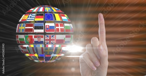 Composition of finger pointing up over illustration of earth formed with national flags
