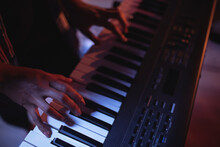 Midsection Of Mixed Race Female Keyboard Player Playing During Concert In Music Venue