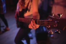 Midsection Of Caucasian Female Bass Guitarist Playing During Concert In Music Venue