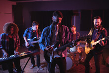 Diverse Music Band With Guitarists, Keyboard Player And Drummer During Concert In Music Venue