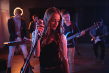 Caucasian Female Singer Holding Retro Microphone At Concert In Music Venue, Music Band Behind Her